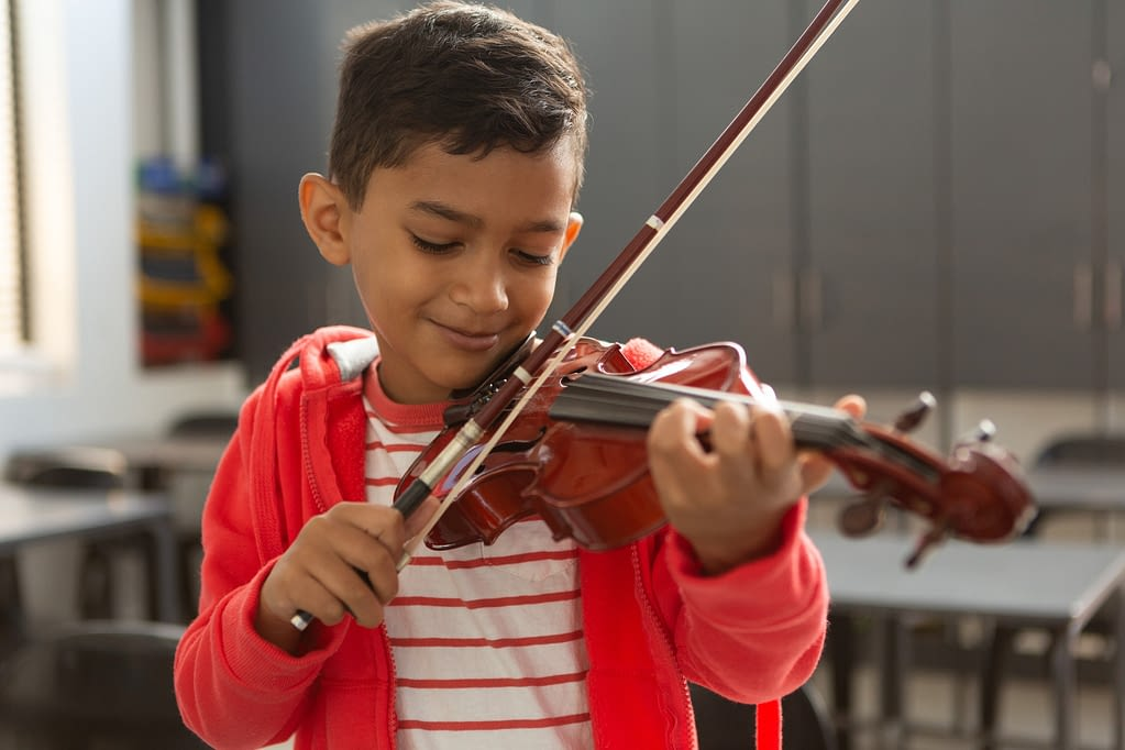 Smiling schoolboy with eyes closed playing violin in classroom at elementary school