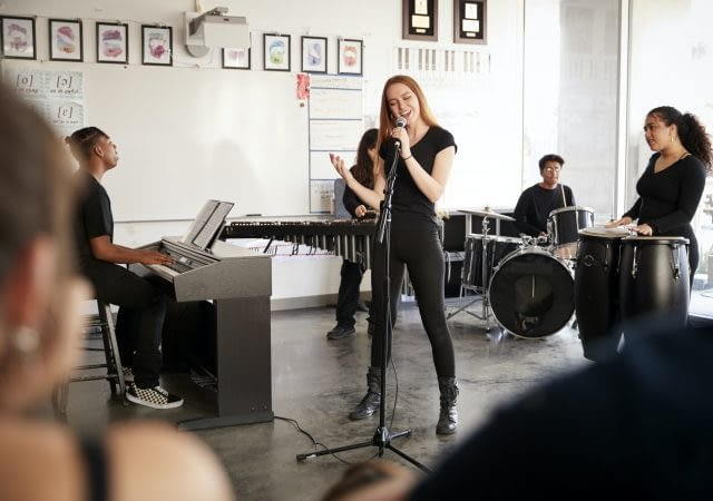 Students At Performing Arts School Playing In Band At Rehearsal