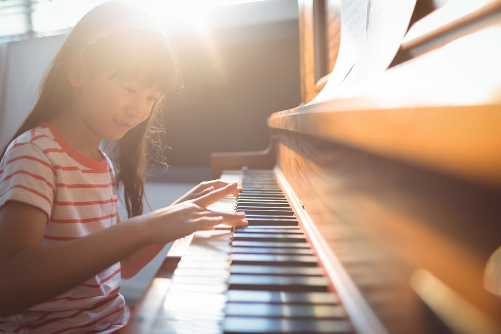Smiling girl practicing piano in classroom