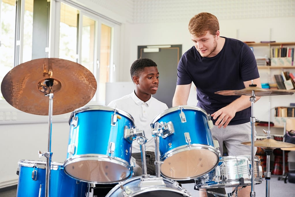 Male Pupil With Teacher Playing Drums In Music Lesson