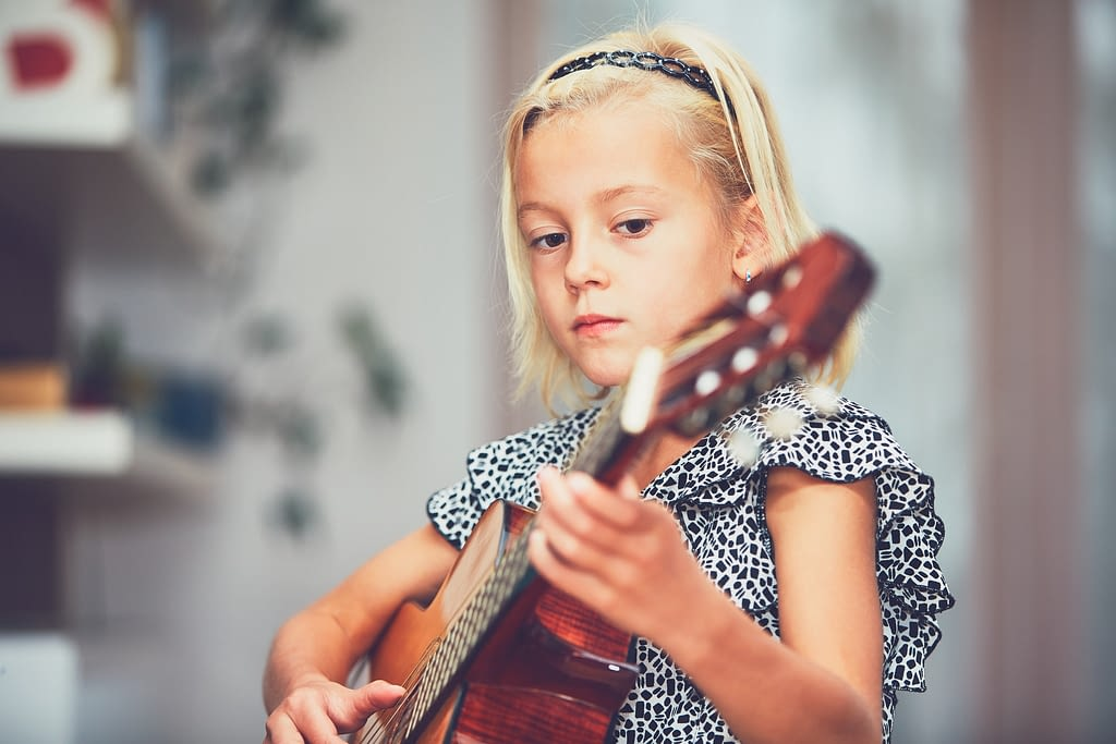 Girl learning to play to the guitar