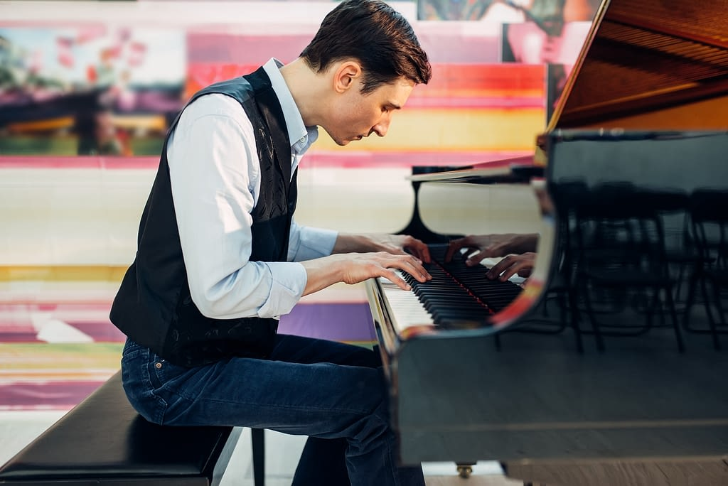Male pianist practicing composition on grand piano