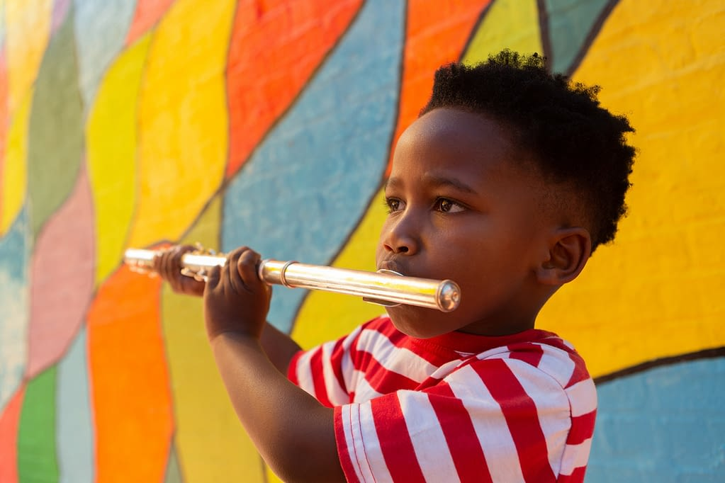 Side view of innocent African-American schoolboy playing flute instrument in the school playground